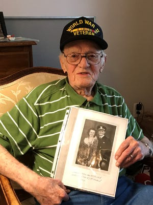 Eugene McDonald, 98, of Westland, holds a 1941 photograph taken during his World War II Navy tenure. He is shown with his first wife Kathryn.