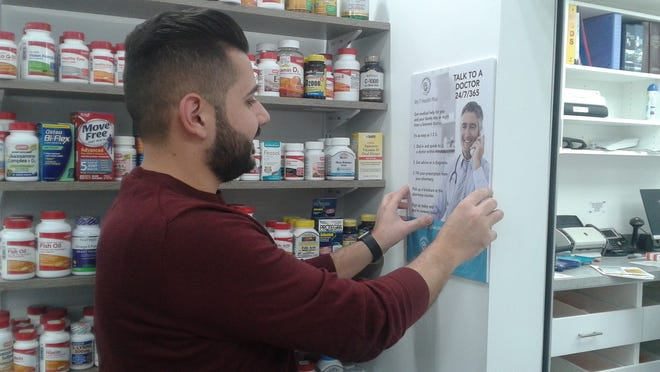 Marwan H. Isa, owner of Lincoln Rx Pharmacy in Oak Park, places a poster about a new Sav-Mor telehealth program in his store.