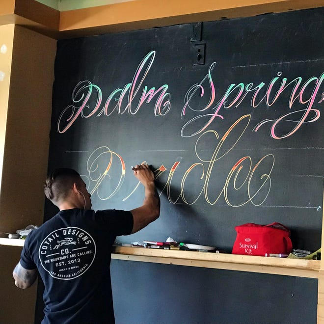 Bartender Ricky Rojas writes on a chalkboard at Chill Bar in Palm Springs on Thursday, Nov. 1.