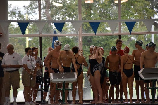 The Gulf Breeze boys and girls 400-yard freestyle relay teams get set for the final races at the District 1-2A swimming championships at the UWF Aquatic Center in November.