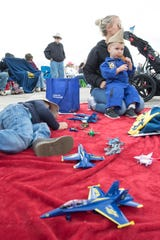 T.J. Miller, 2, of Pensacola takes a break on the lap of his mother, Olivia Miller, to enjoy a chicken finger while his Charles Edgar V, also 2, lays among their squadron of toy airplanes Friday during the Blue Angels Homecoming Show at Naval Air Station Pensacola.