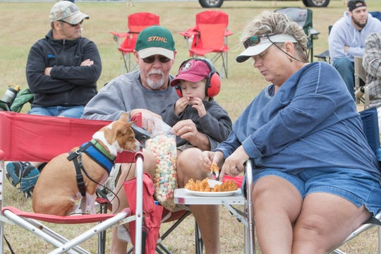 Buddy is ever hopeful that his owners, from left, Gainer Comerford, 3-year-old Sawyer Powell and Leane Comerford will share some of their food with him Friday at the Blue Angels Homecoming Show at Naval Air Station Pensacola.