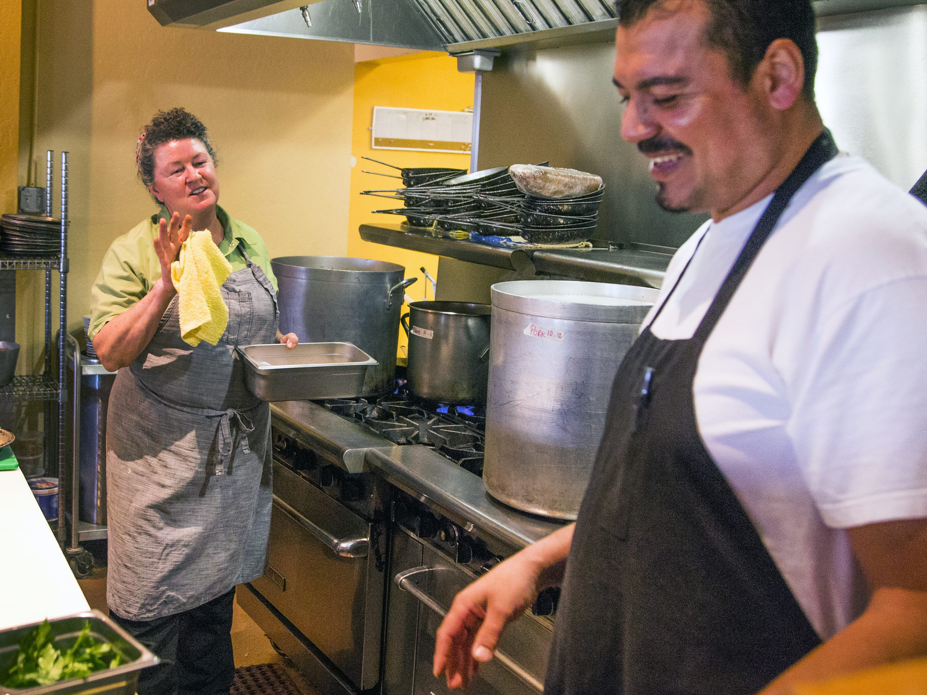 Chrysa Robertson works with cook Gregory Soto, right, in the kitchen of her restaurant, Rancho Pinot, in Scottsdale, Tuesday, Oct. 16, 2018.