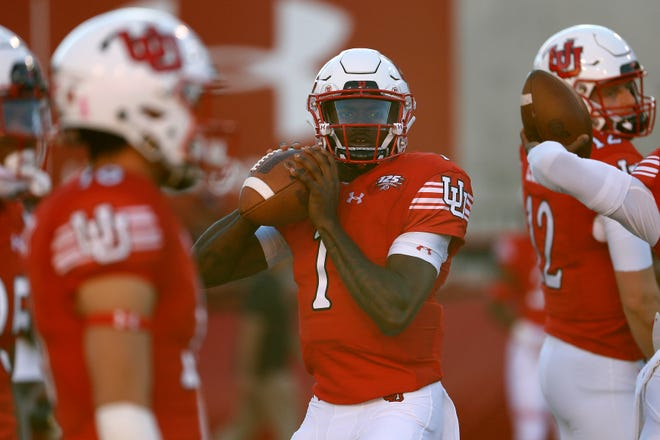 Utah quarterback Tyler Huntley (1) warms up before a game against USC at Rice-Eccles Stadium.