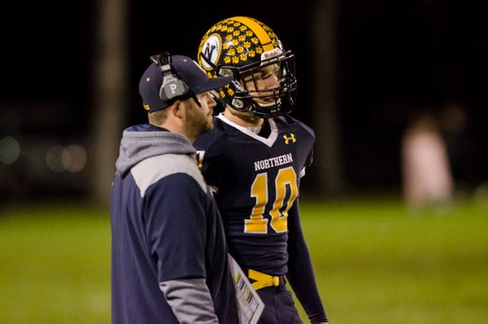 Port Huron Northern head football coach Larry Roelens, left, talks with quarterback Seth Klink between plays in the first quarter of their Division 2 finals match against St. Clair Shores Lakeview Friday, Nov. 2, 2018 at Memorial Stadium in Port Huron.