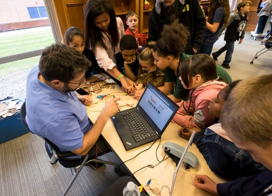 John Churchville, from the Ann Arbor Hands-On Museum, shows a group of students how electrical currents can be used to make sounds Friday, Nov. 2, 2018 at SC4's Experience Center in the Clara E. Mackenzie Building