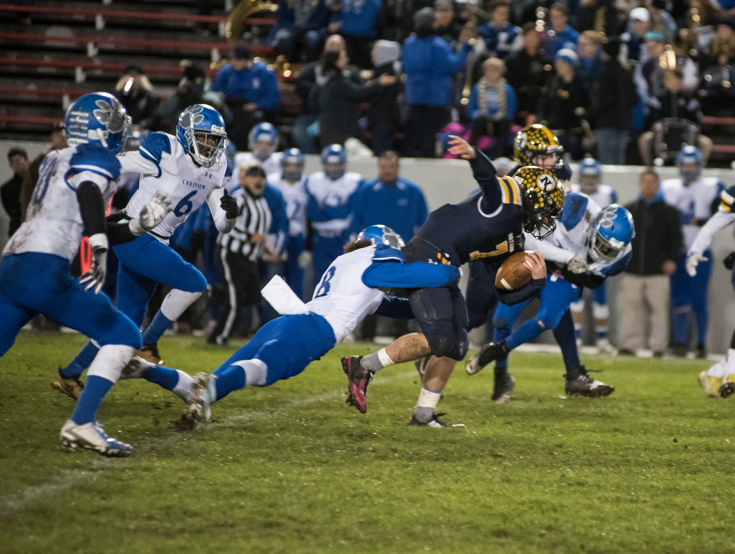 Port Huron Northern High School running back Theo Ellis is tackled by St. Clair Shores Lakeview's Isaiah Robinson (8) in the first quarter of  their Division 2 finals match Friday, Nov. 2, 2018 at Memorial Stadium in Port Huron.