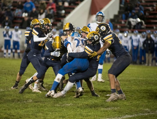 Port Huron Northern High School linebacker Luke O'Hare grabs St. Clair Shores Lakeview's Evan Rochon (20) as he runs the football during their Division 2 finals match Friday, Nov. 2, 2018 at Memorial Stadium in Port Huron.