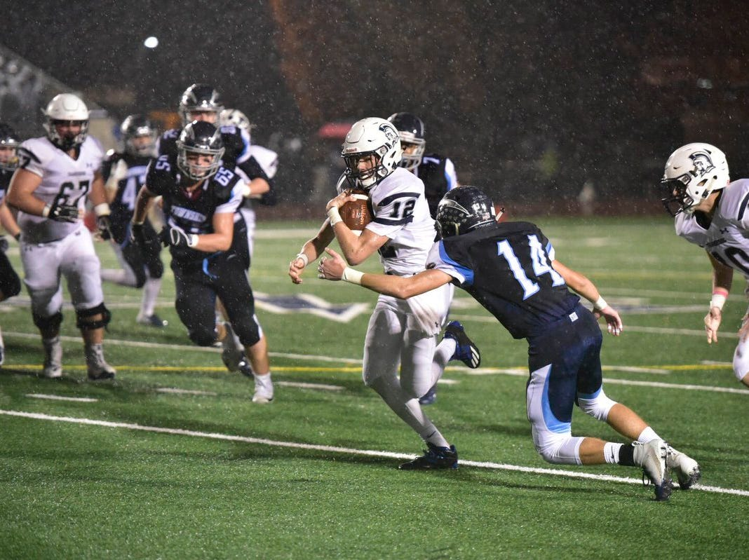 Chambersburg quarterback Brady Stumbaugh tries to avoid a tackle by Manheim Township's Matt Mikulka.