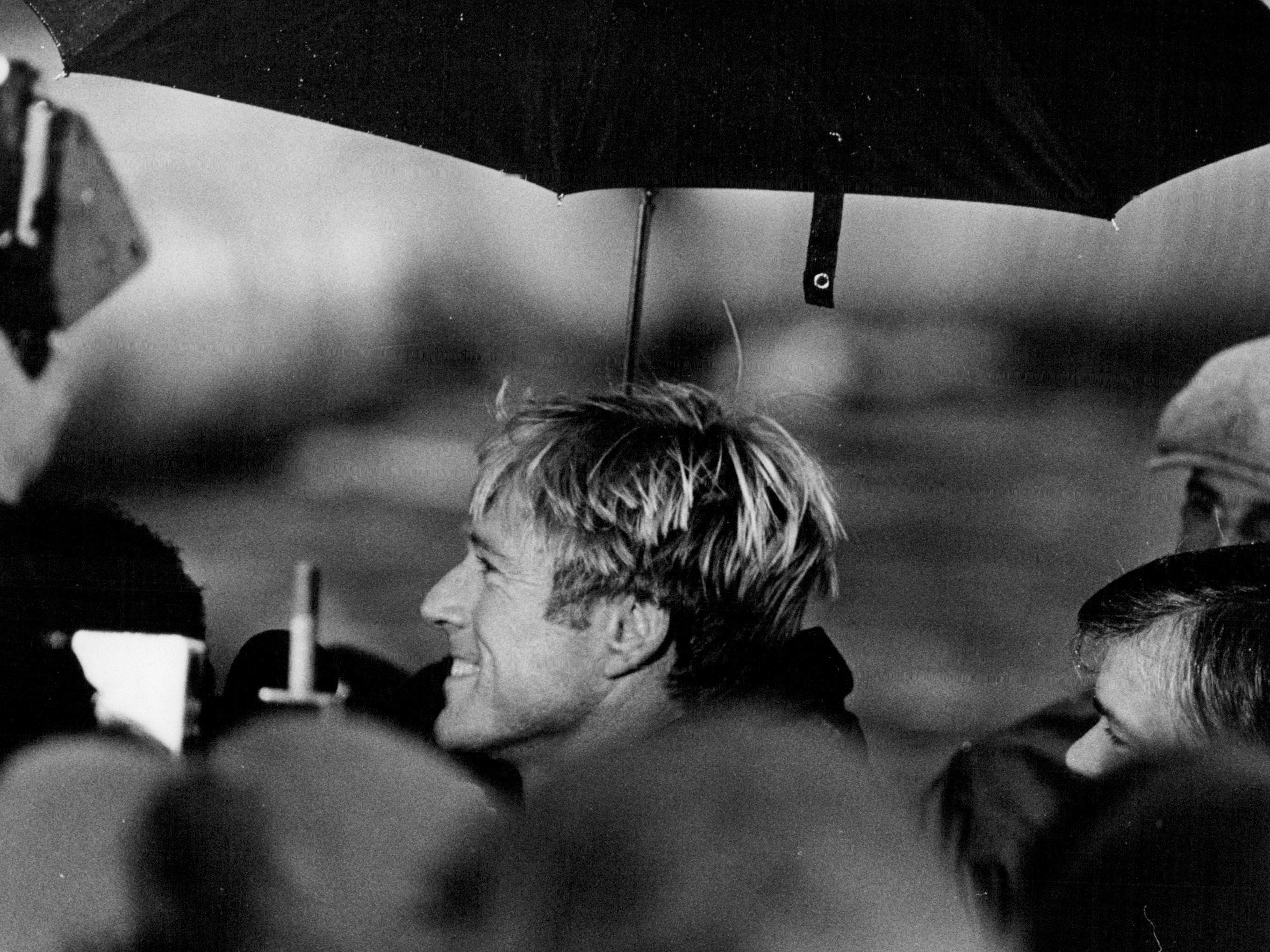 "In this 1983 photo, actor Robert Redford stand beneath an umbrella while thanking the extras who were there to be in his movie, ""The Natural."" The scenes were filmed at Buffalo Stadium and more than 900 from Rochester were part of that crew."