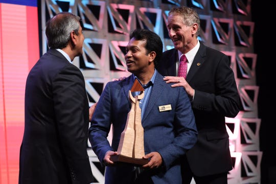 Faheem A. Masood, president and CEO of ESL Federal Credit Union, left, and Rochester Chamber of Commerce president and CEO Robert Duffy, right, present the top Top 100 award to Sameer Penakalapati of Avani Technology Solutions inc.