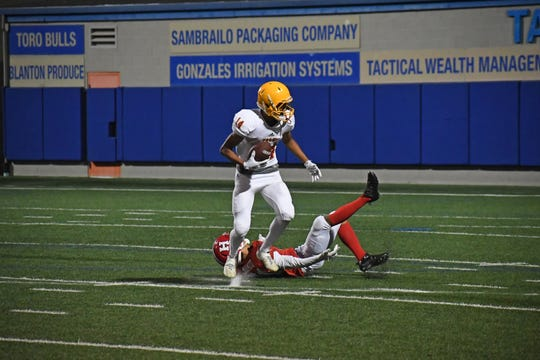 Palma wide receiver Micah Servano Olivas (14) breaks a tackle on his way to a touchdown.
