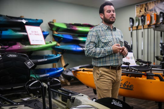 Colby Chesshire walks through the kayaks on display Friday, Nov. 2, 2018, at Happy Trails Outdoor Goods & More.