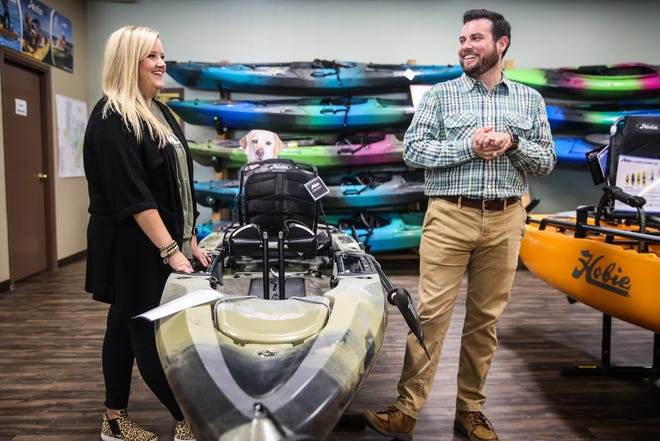 Owners Colby and Jessica Chesshire chat over a kayak Friday, Nov. 2, 2018, at Happy Trails Outdoor Goods & More.