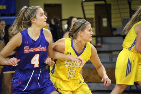 Macy Miller (12) and Lexi Schneider of Mary battle for position Thursday night at Frost Arena