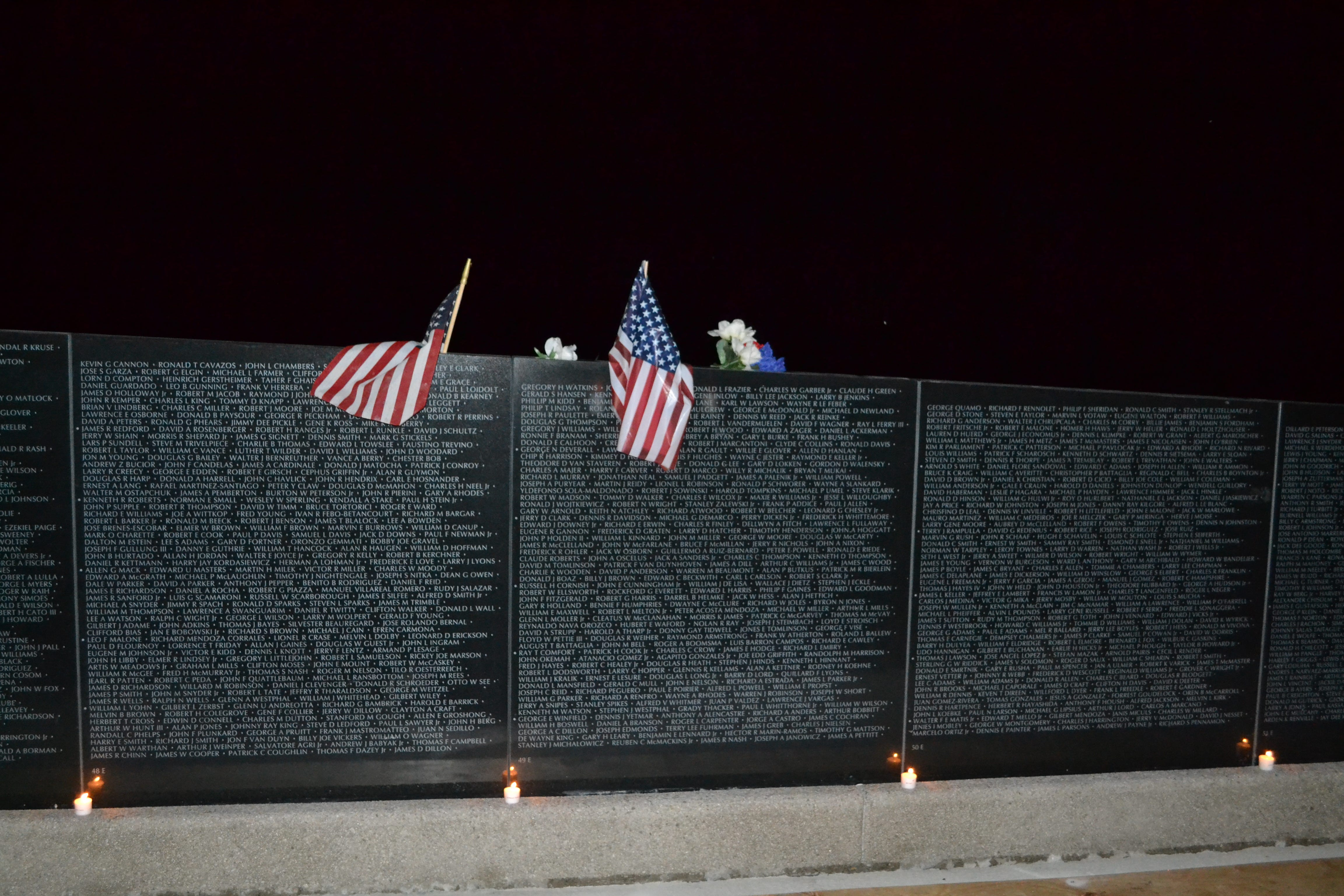 Candles, flags and flowers adorn the recently installed panels at Missouri's National Veterans Memorial during a candlelight ceremony Friday, Sept. 21, 2018, in Perryville.