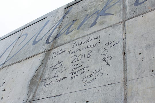 Visitors signing the wall bridged many generations, from World War II veterans to a group of soon-to-be graduates from a local industrial technology program.