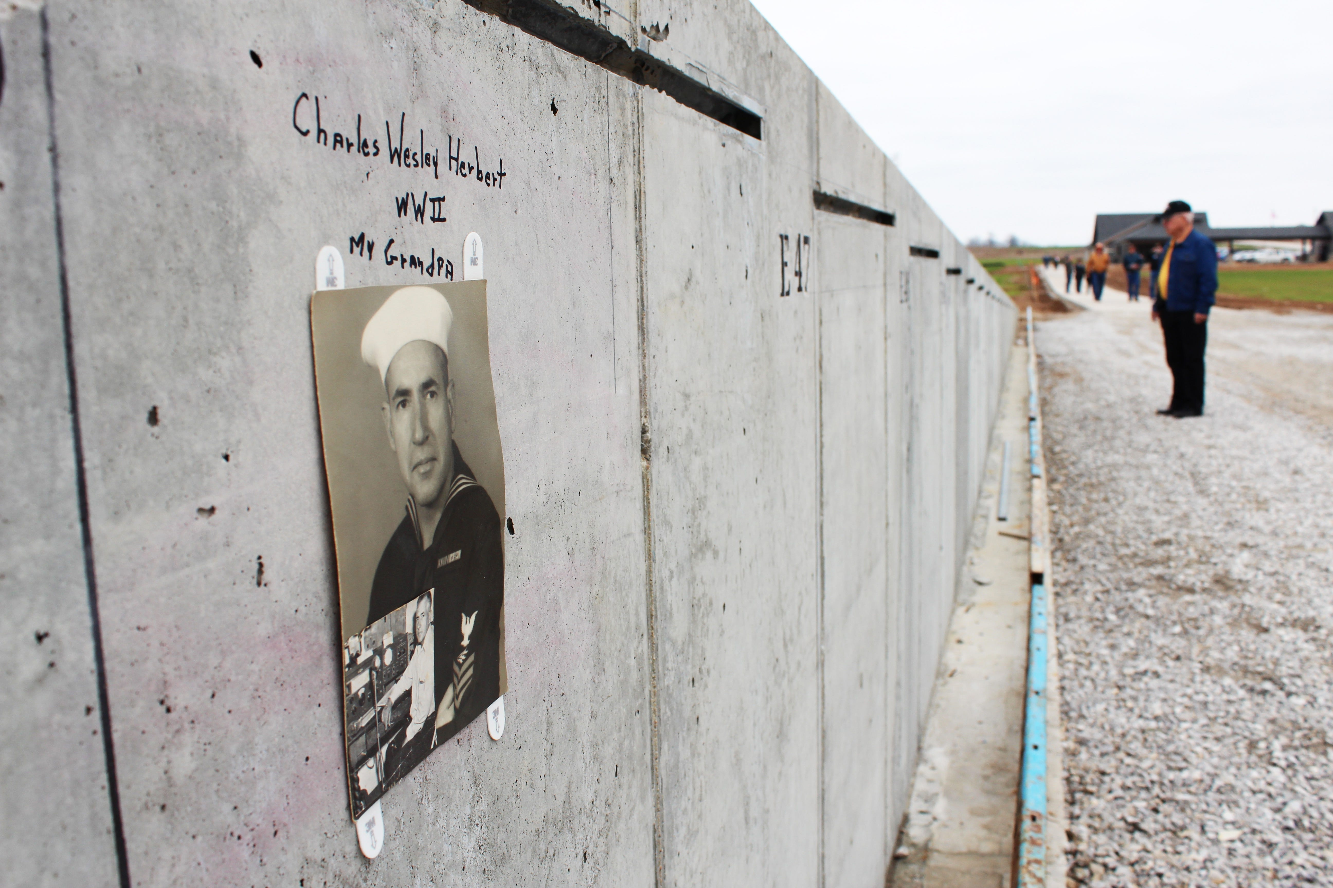 """Some visitors to the Missouri's National Veterans Memorial site for the """"Mark of Remembrance"""" event included photos of their loved ones. The signatures and photos were left in place as the panels were installed, making them a permanent, if hidden, part of the monument."""