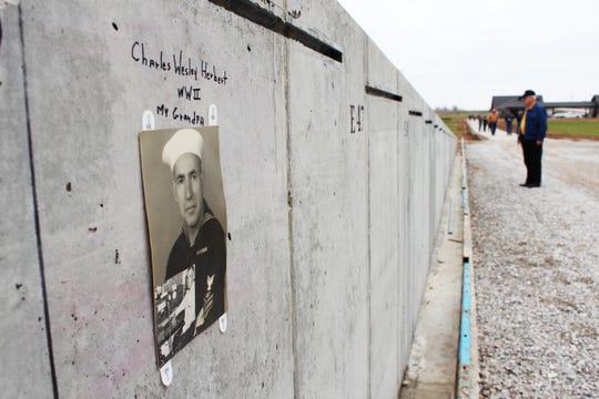 "Some visitors to the Missouri's National Veterans Memorial site for the ""Mark of Remembrance"" event included photos of their loved ones. The signatures and photos were left in place as the panels were installed, making them a permanent, if hidden, part of the monument."