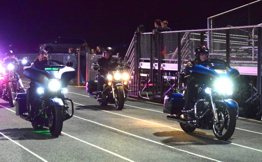 Members of the Rolling Thunder motorcycle group drive around the Buffalo Gap High School track during the school's Military and First Responder Appreciation Night on Thursday, Nov. 1, 2018, in Swoope, Va.