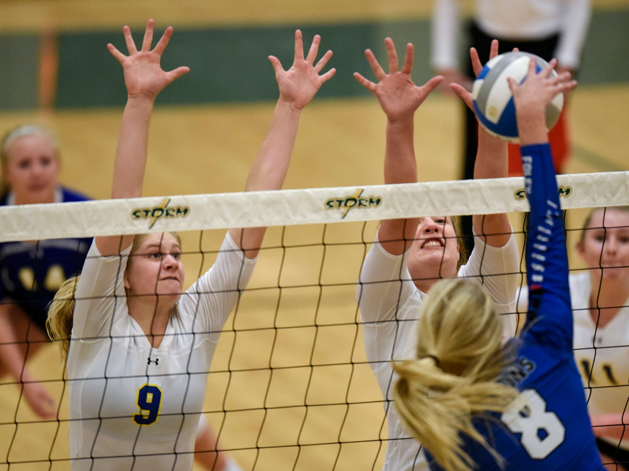 Cathedral's Meg Januschka and Gabby Heying leap for a block during the Section 6-2A volleyball semifinals Thursday, Nov. 1, at Sauk Rapids-Rice High School.