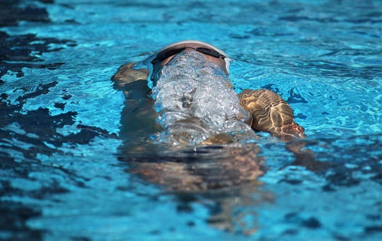 Maclay's Wade Eastman makes his turn on a backstroke swim and comes out of the water for air during the District 1-1A swimming and diving meet at Morcom Aquatics Center on Wednesday, Oct. 21, 2018.