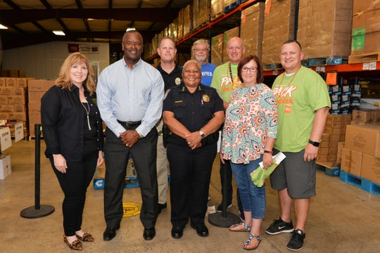 Treasure Coast Food Bank CEO Judy Cruz, left, State Rep. Larry Lee, Fort Pierce Police Department's Robert Ridle and Diane Hobley-Burney, Jeff Bremer, Mark Satterlee, St. Lucie County Commissioner Linda Bartz and Fort Pierce City Commissioner Jeremiah Johnson at Treasure Coast Food Bank's fourth annual Pack The House event on Oct. 26-27.