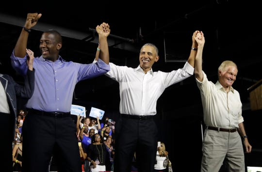 Former President Barack Obama, center, raises arms with Democratic gubernatorial candidate Andrew Gillum, left, and U.S. Sen. Bill Nelson, D-Fla., right, during a campaign rally, Friday, Nov. 2, 2018, in Miami.