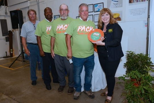 Judy Cruz, right, presents a plate to American Public Works Association members Frank Knott, Milton Leggett, Richard Perkins and Bob Carlsen for their participation in Treasure Coast Food Bank's Pack The House event on Oct. 26-27.