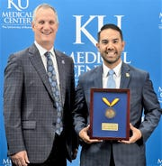 Nicholas Tejeda, El Paso market CEO for The Hospitals of Providence, with his University of Kansas Medical Center alumni award presented Oct 5 from Dr. Robert Simari, executive vice chancellor of the KU Medical Center and executive dean of the KU School of Medicine.