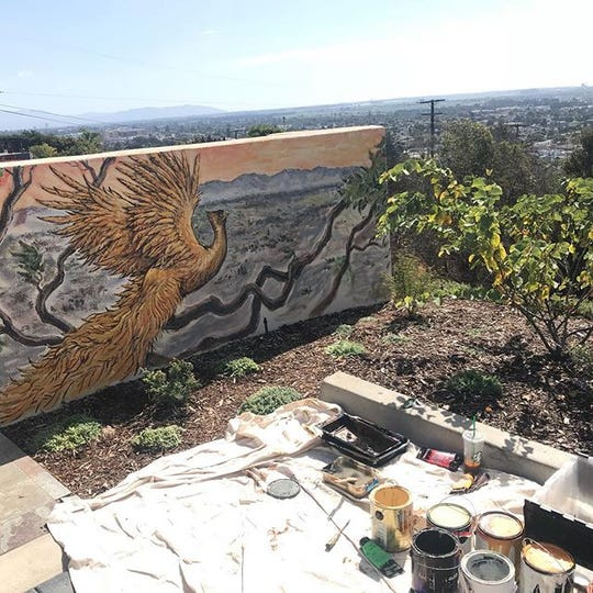 A recently painted mural by Ryan Carr decorates a wall in the restored yard of Betsy Chess, of Ventura. The image of a phoenix is a metaphor for Ventura's resolve to rise out of the ashes of the Thomas Fire.