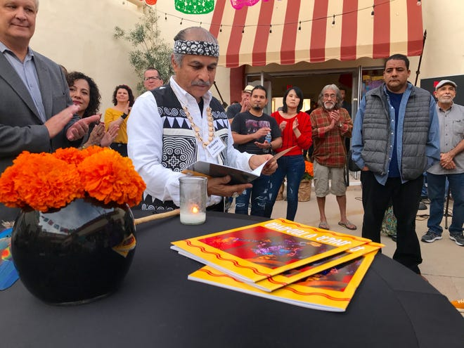 """Latino advisory committee member Roberto Vargas examines a copy of the new """"Ayer y Todavia"""" catalog, which documents the Museum of Ventura County's Chicano art exhibit of the same name that took place last year."""