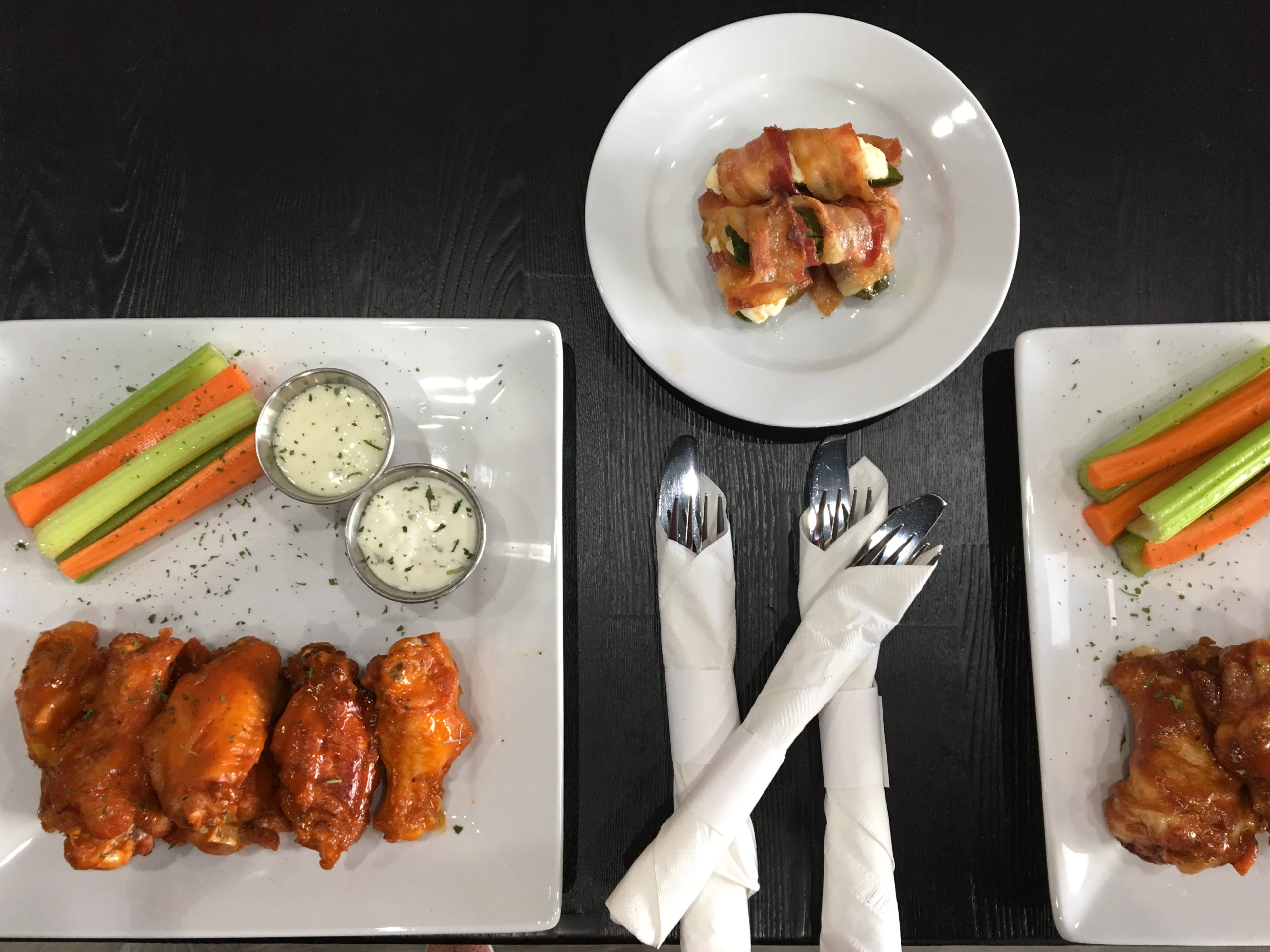 Orders of buffalo wings, left, barbecue wings, right, and bacon-wrapped roasted jalapenos, center top, are seen at Tap'd Ventura.