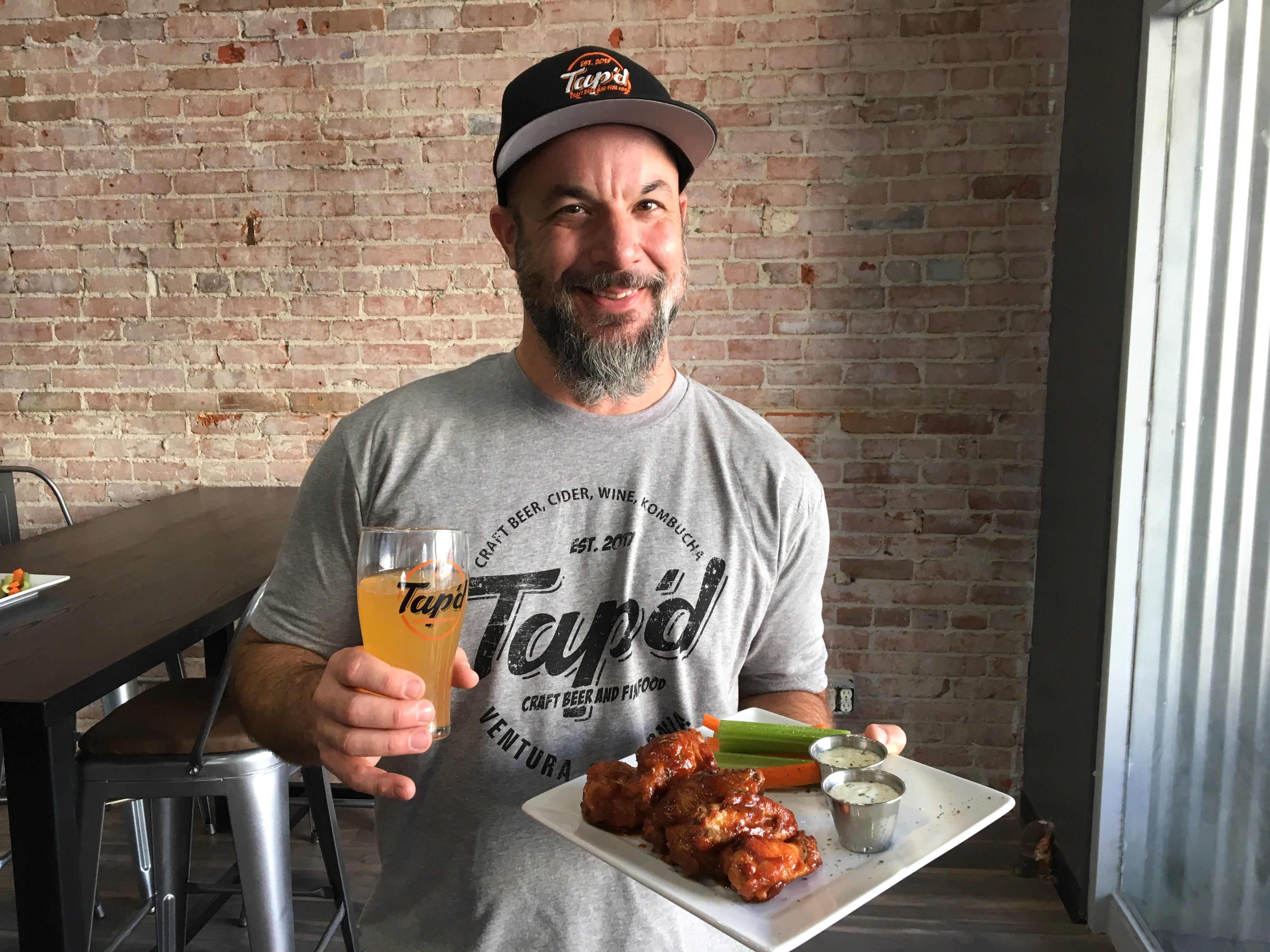 Matt Burin, executive chef at Tap'd Ventura, poses with a pint of beer and a plate of wings. The menu at the self-service taproom also includes burgers, salads, desserts and poutine, for which Burin imports gravy from his native Canada.
