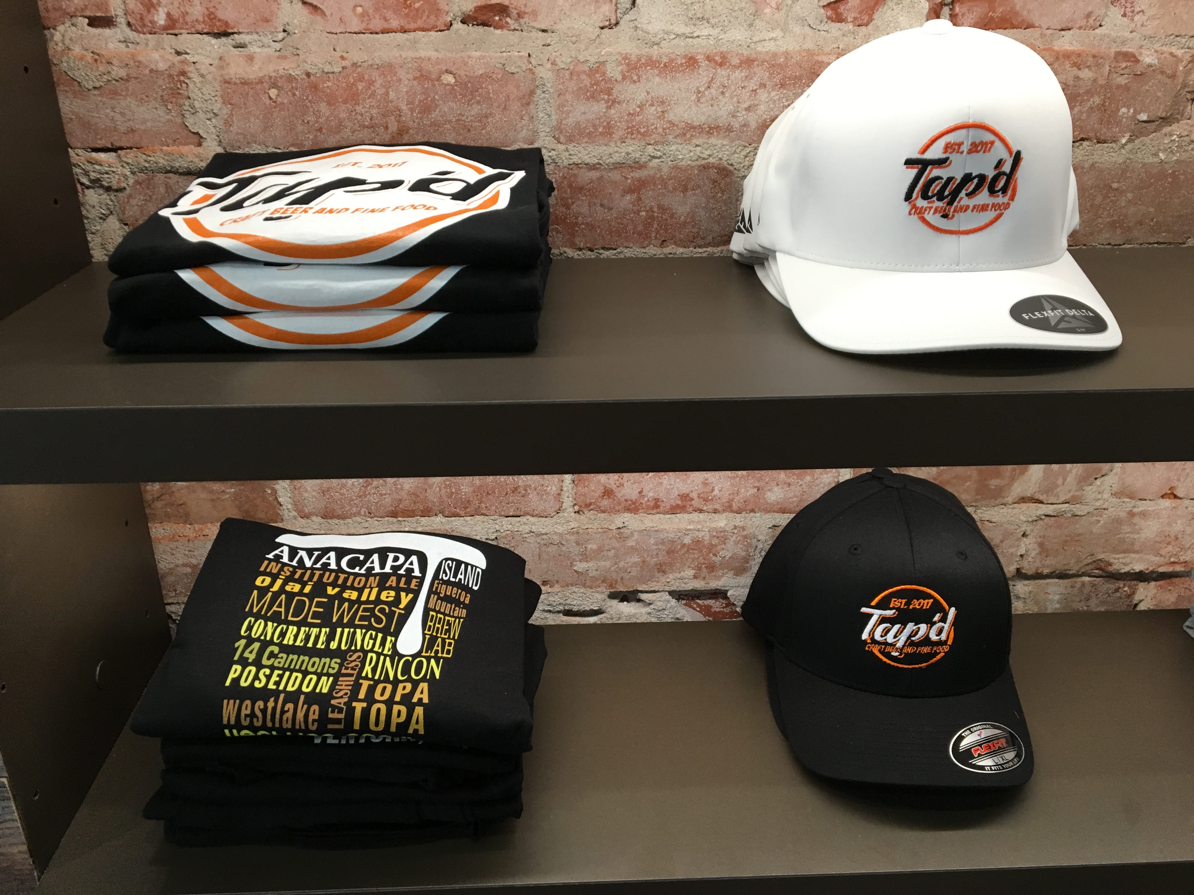 Logo hats and T-shirts are seen on the shelves at Tap'd Ventura.