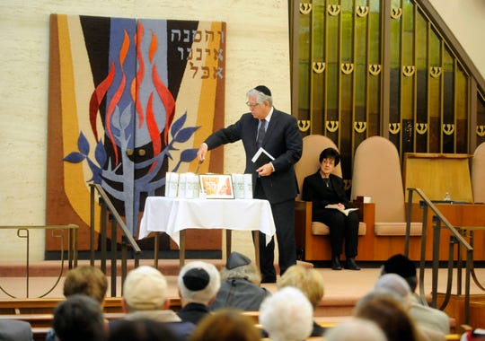 Rabbi Bradley Bleefled lights a candle honoring the Tree of Life Synagogue victims at Beth Israel Congregation on Thursday, November 1, 2018.