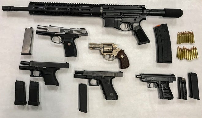 Detectives confiscated a total of five handguns and one assault rifle, as well as hundreds of rounds of ammunition.