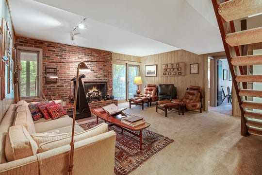 A lower level den at 110 Thissell in Greenville has a brick fireplace and original wood paneling.
