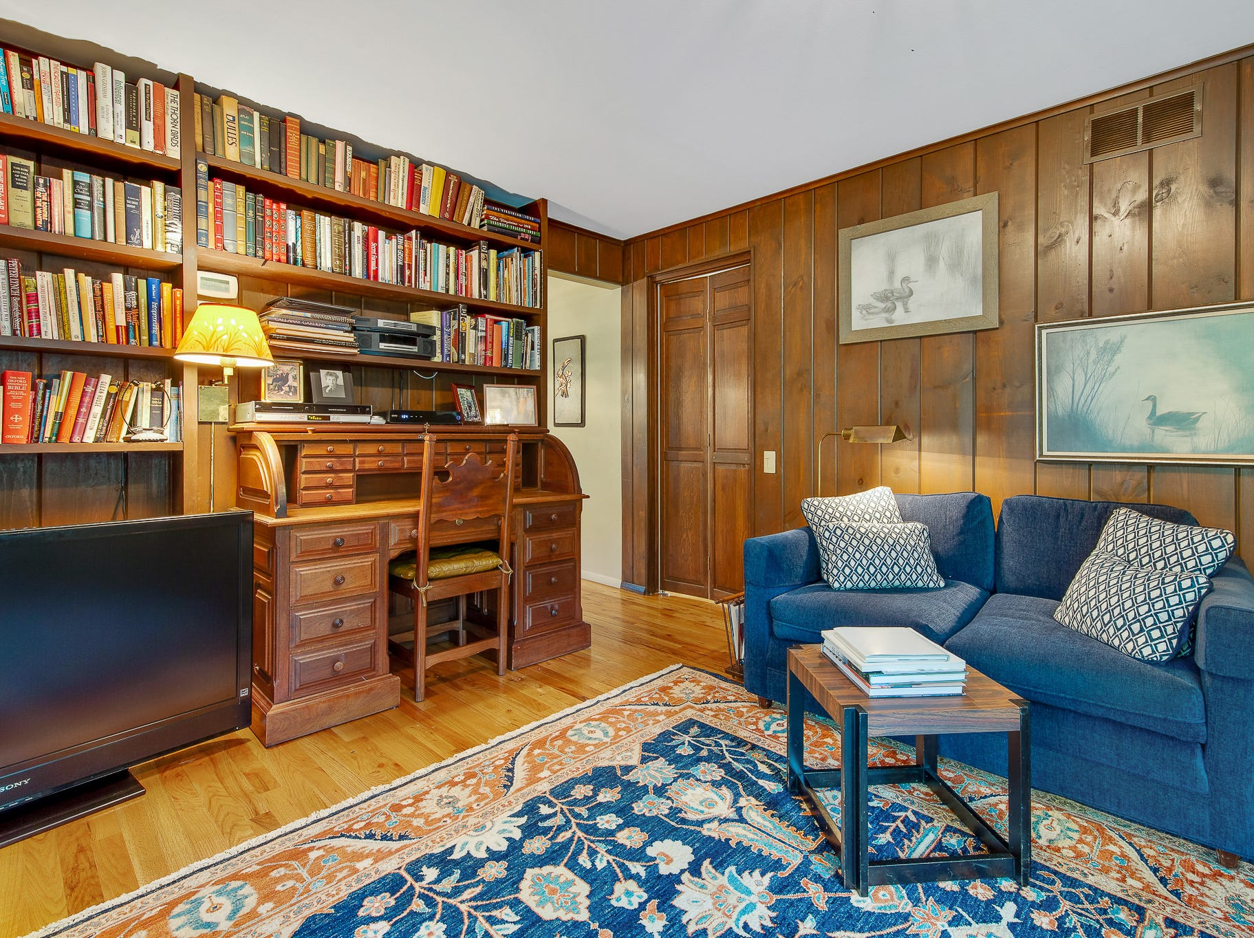 A den at 110 Thissell in Greenville has the original wood paneling.