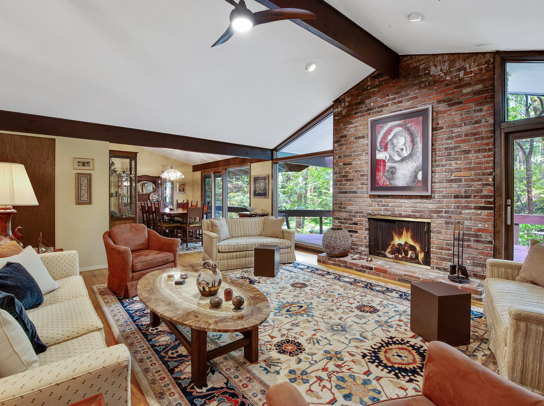 The open living area at 110 Thissell in Greenville has a pitched ceiling and brick fireplace.