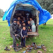 A family of 10, living in a small truck, flees the Syrian government's bombardment of their village in 2013.