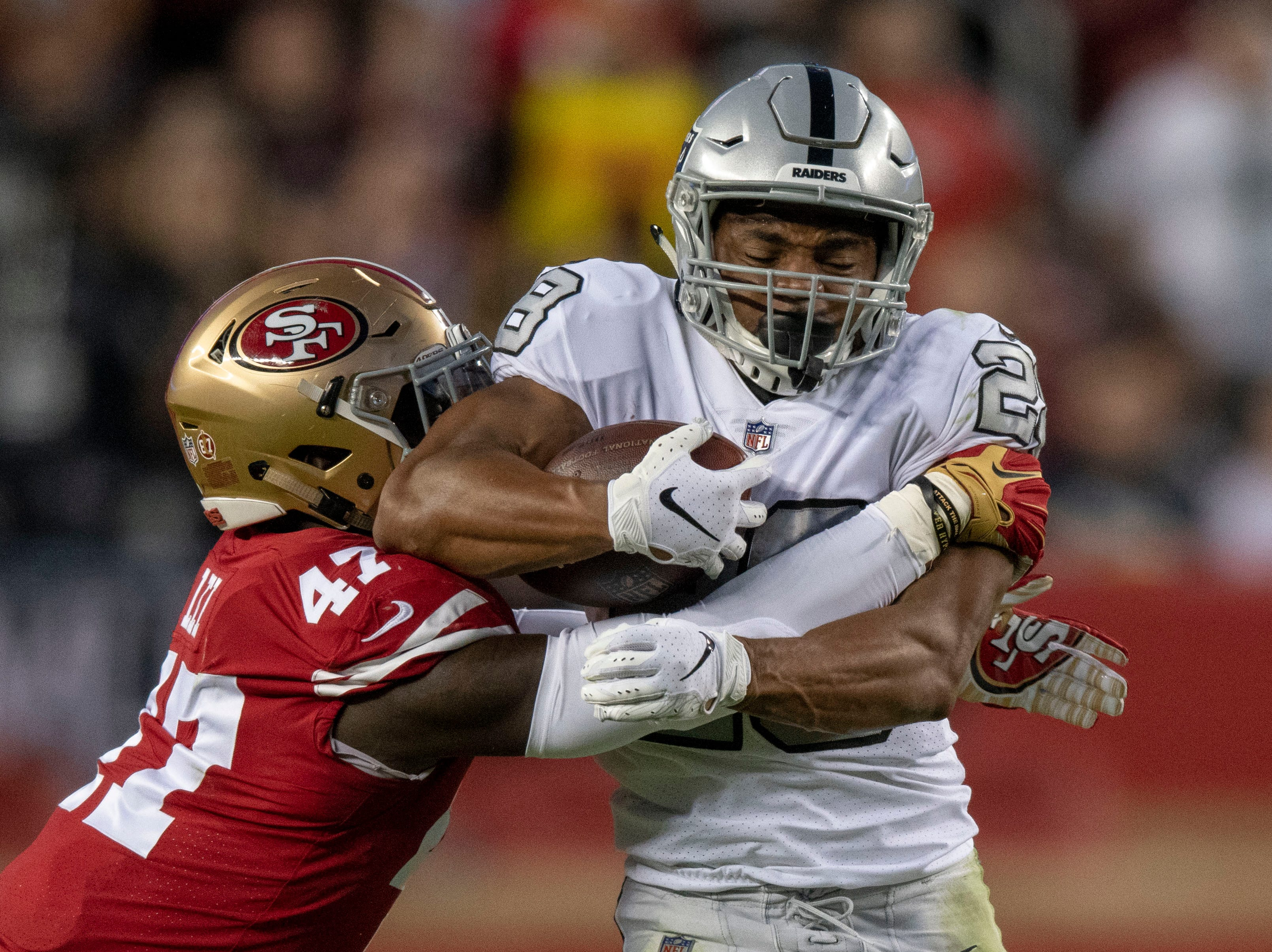 Oakland Raiders running back Doug Martin (28) is tackled by San Francisco 49ers outside linebacker Elijah Lee (47) during the second quarter at Levi's Stadium.