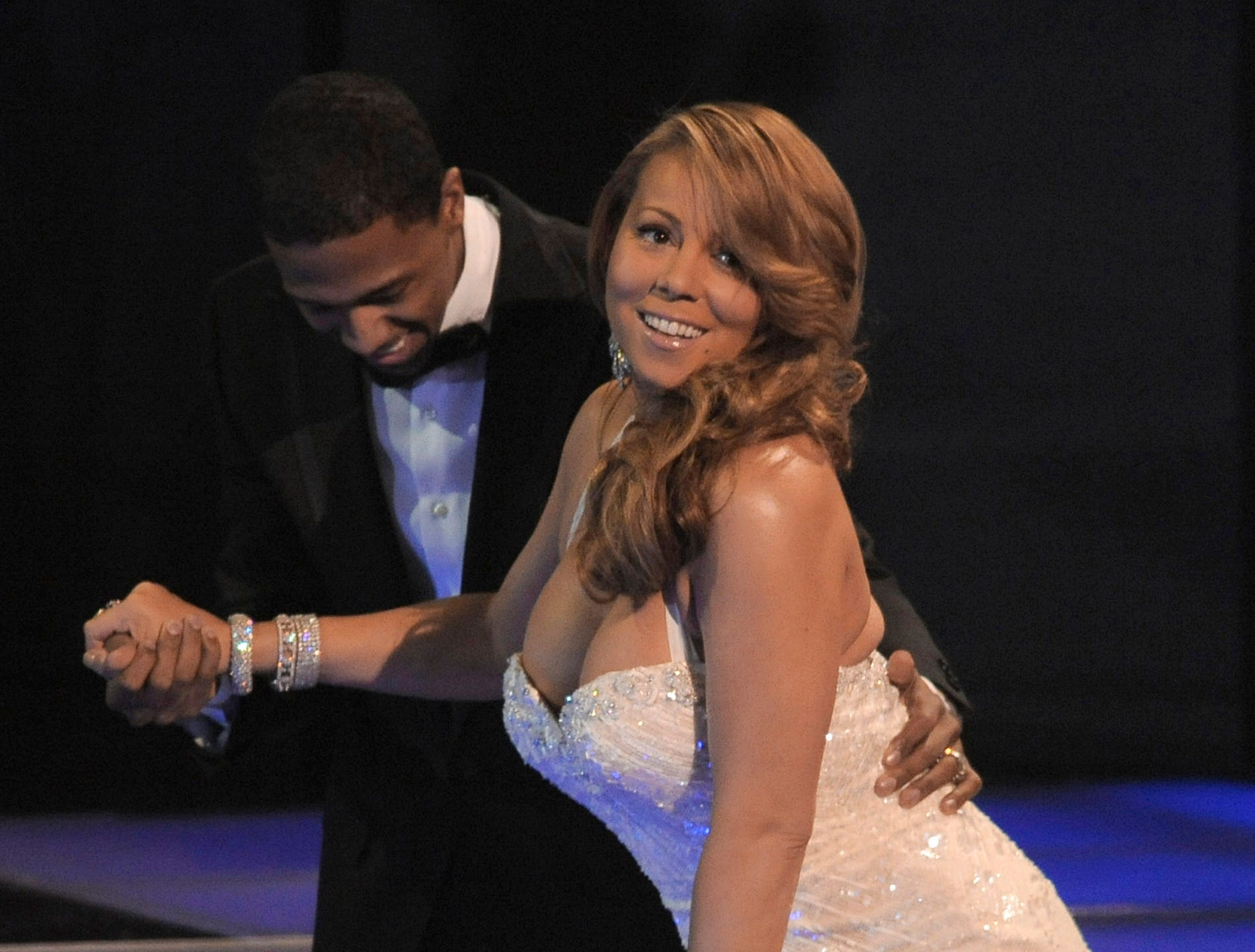 Nick Cannon helps Mariah Carey go on stage to accepts the award for best R&B artist at the People's Choice Awards on Wednesday Jan. 6, 2010, in Los Angeles. (AP Photo/Chris Pizzello) ORG XMIT: CADC138