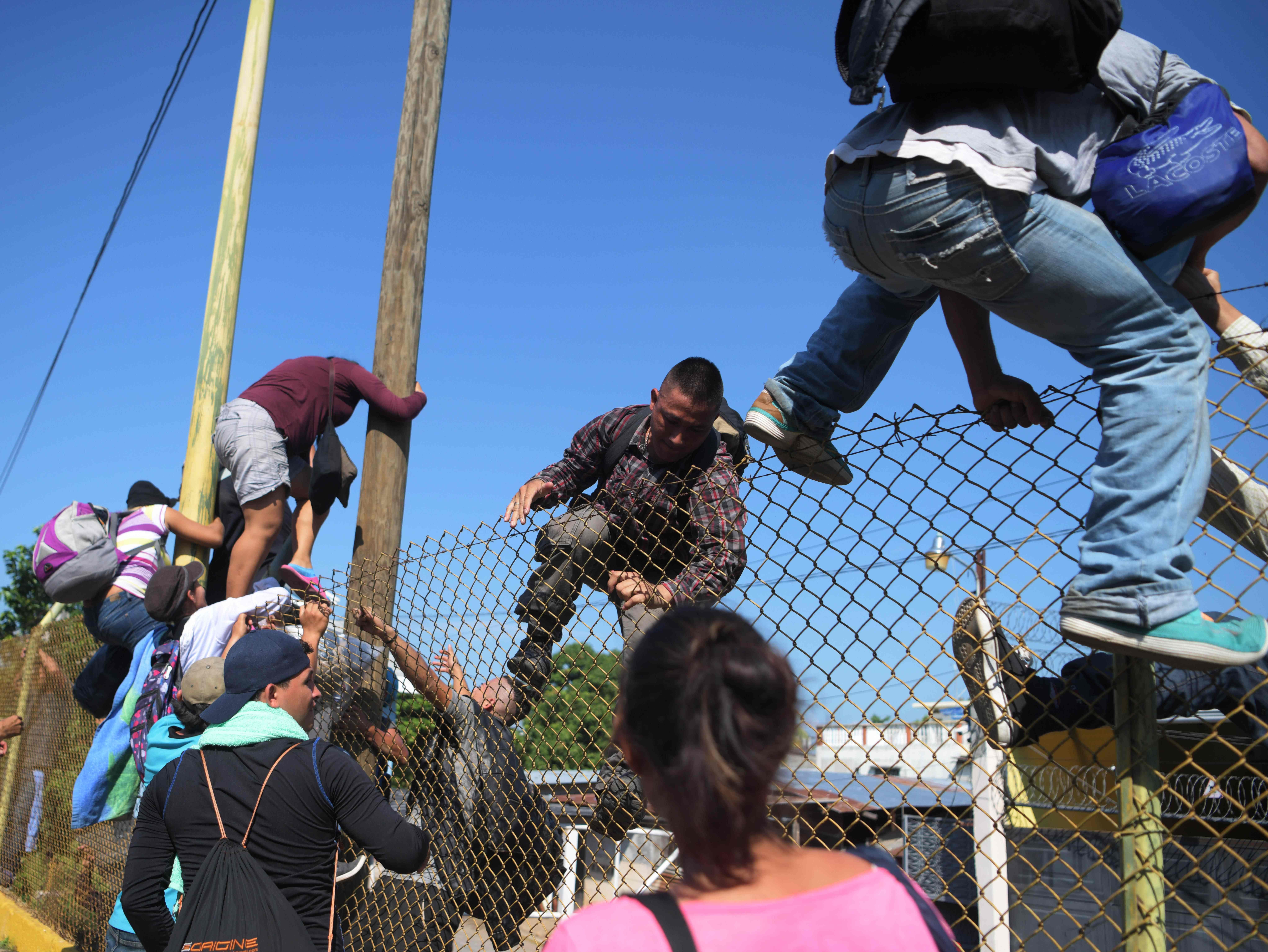 Salvadorian migrants climb and jump over a fence to get to the Guatemala-Mexico international border bridge in Ciudad Tecun Uman, Guatemala, on Nov. 2, 2018.