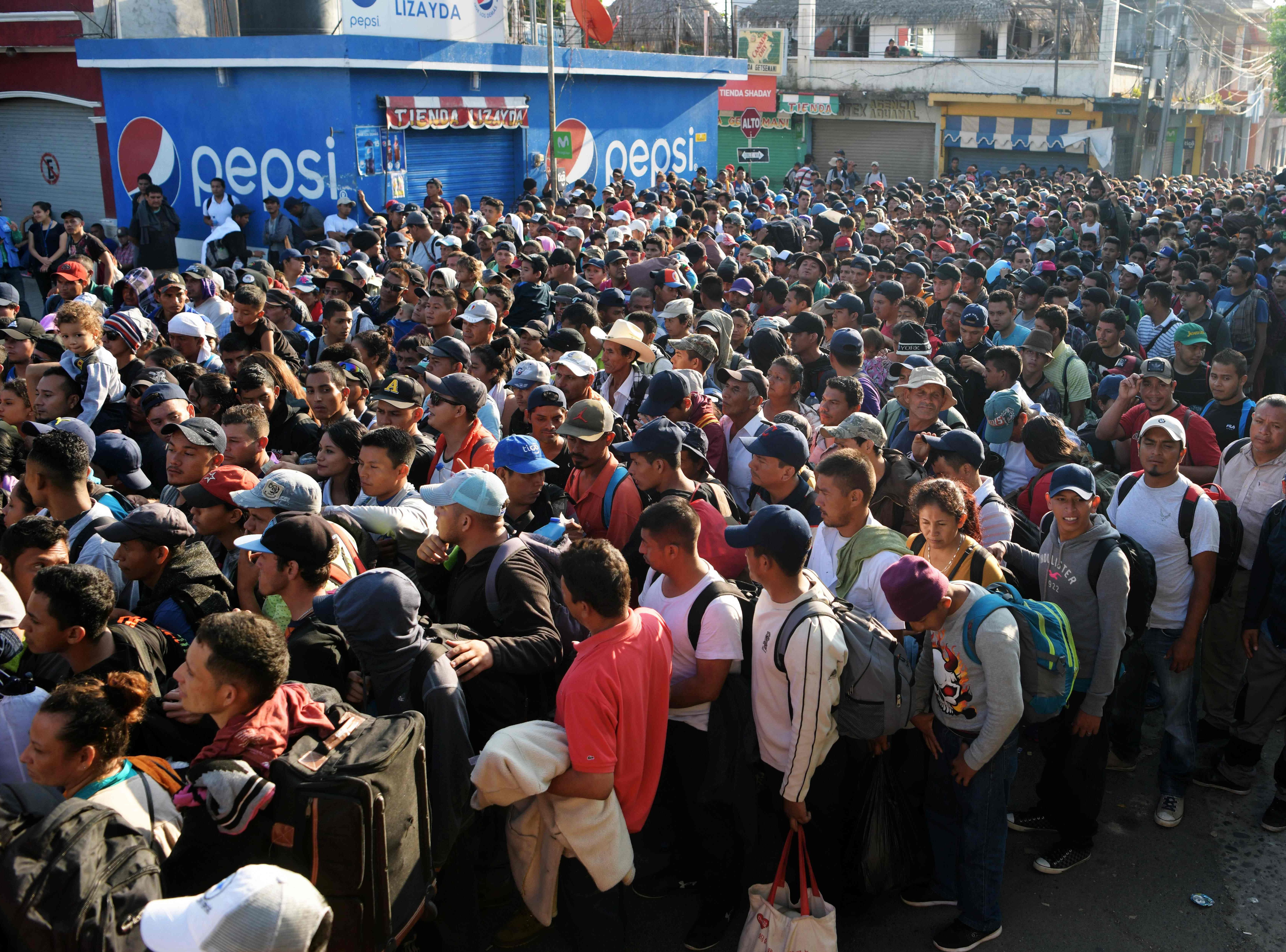 Salvadorian migrants wait to enter the Guatemala-Mexico international border bridge next to the customs building in Ciudad Tecun Uman, Guatemala, on Nov. 2, 2018.
