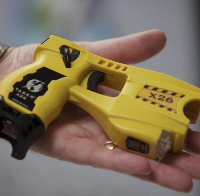 BLACKPOOL, UNITED KINGDOM - MAY 16:  A representative from Taser International shows the companies latest X26 stun gun during the Police Federation Conference at Winter Gardens on May 16, 2007 in Blackpool, England. British Home Secretary John Reid announced today that more Taser guns could be deployed on the streets of the UK by frontline police officers. The Taser's which stun a person with up to 50,000 volts, and can currently only be carried by armed response officers have some under harsh criticism from Amnesty International  who claim more than 70 deaths in Canada and America have been linked to the weapon.  (Photo by Christopher Furlong/Getty Images)