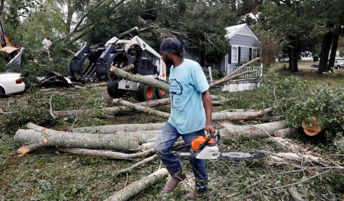 The sound of chainsaws whine through a neighborhood in Natchez, Miss., as cleanup begins following a tornado that hit early on Nov. 1, 2018. At least 11 tornadoes have been confirmed by National Weather Service surveyors so far in Louisiana and Mississippi as part of a storm system that moved across the region.