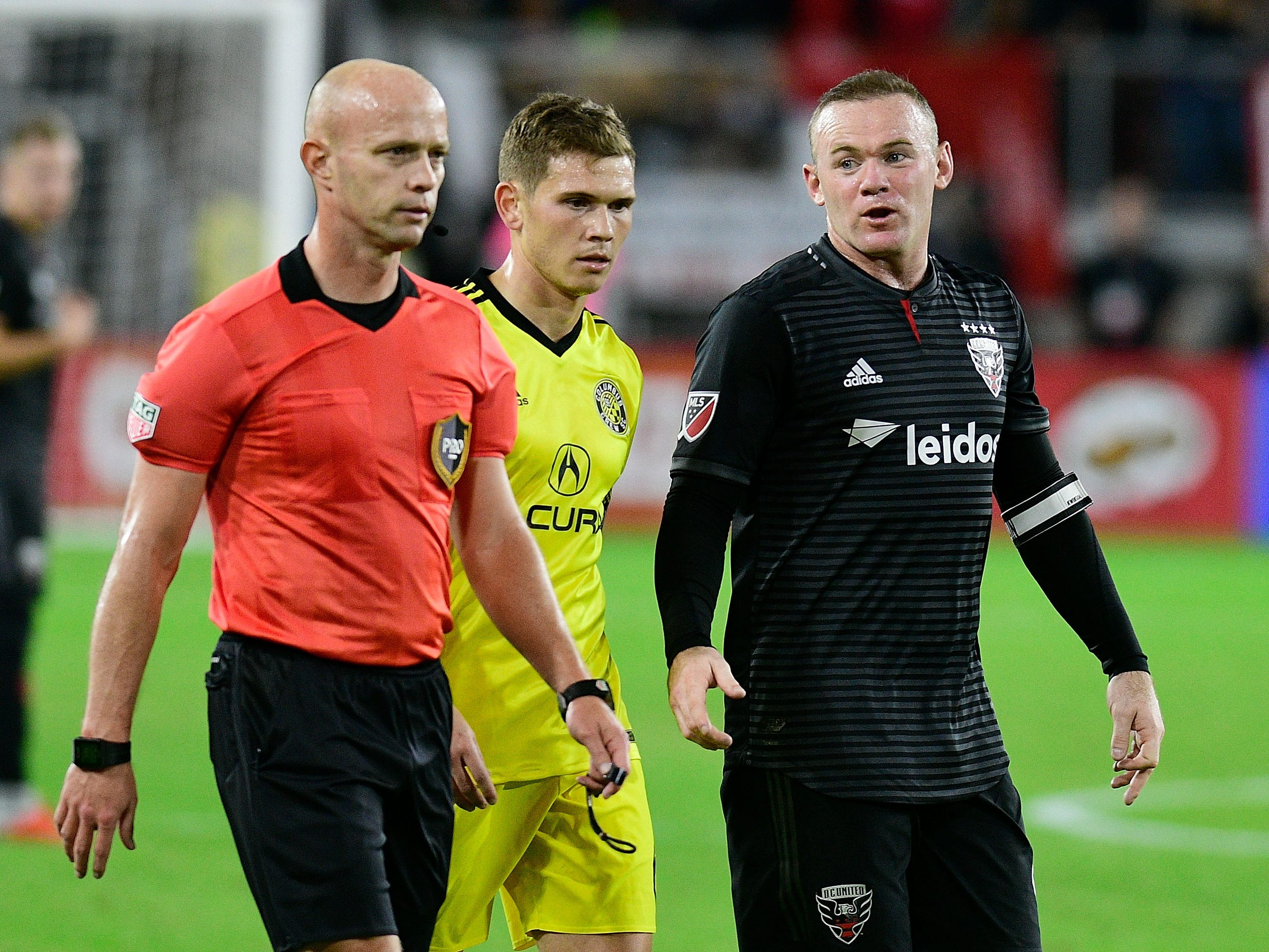 D.C. United's Wayne Rooney talks to referee Allen Champman during the second half against the Columbus Crew at Audi Field.