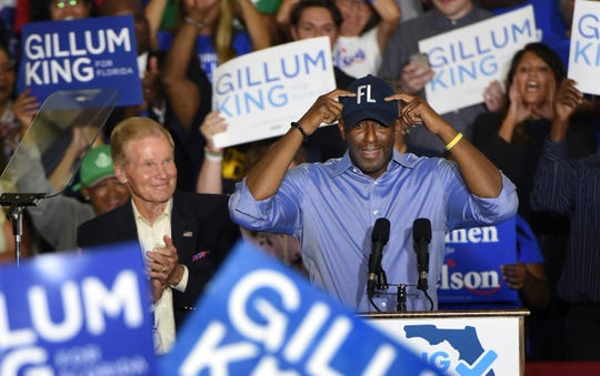 Florida Gubernatorial Democratic candidate Andrew Gillum puts on his FL ball cap as Senator Bill Nelson looks on during a rally Monday, Oct. 22, 2018 in the Field House at the University of North Florida in Jacksonville, Fla. (Bob Self/Florida Times-Union via AP) ORG XMIT: FLJAJ101