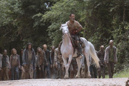 With zombie walkers in pursuit, Rick (Andrew Lincoln) mounts a horse after extricating himself from a rebar puncture on AMC's 'The Walking Dead.'